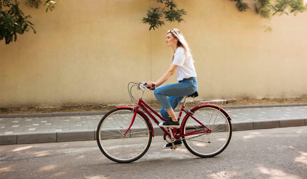 Mujer rubia con pelo largo vestida con una camisa blanca y tejamos montando en una bicicleta roja