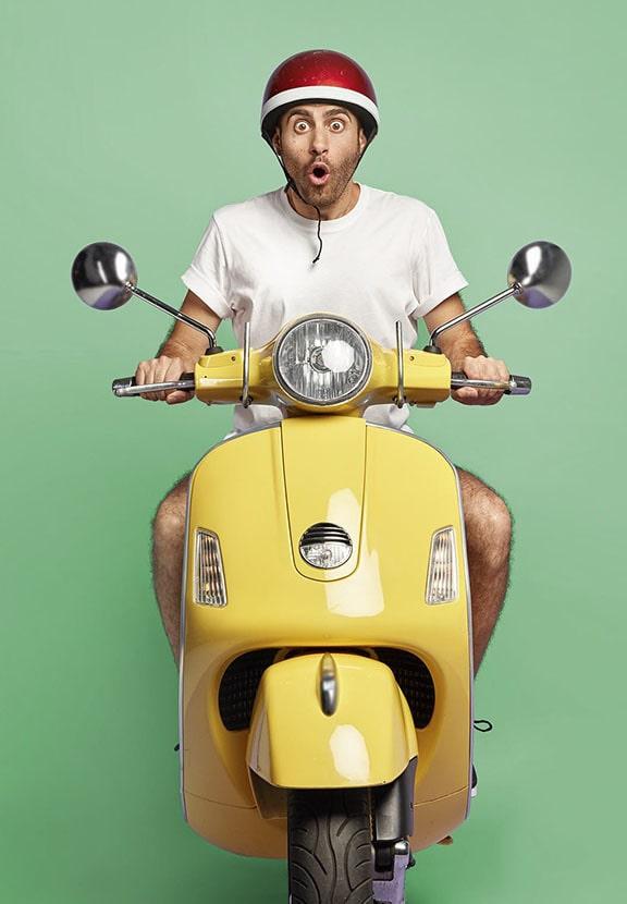 Hombre de cara sorprendida con un casco rojo montando una moto amarilla