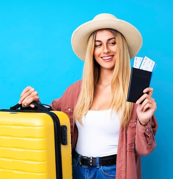 Mujer rubia de pelo largo con un sombrero sosteniendo billetes de avión y una maleta amarilla