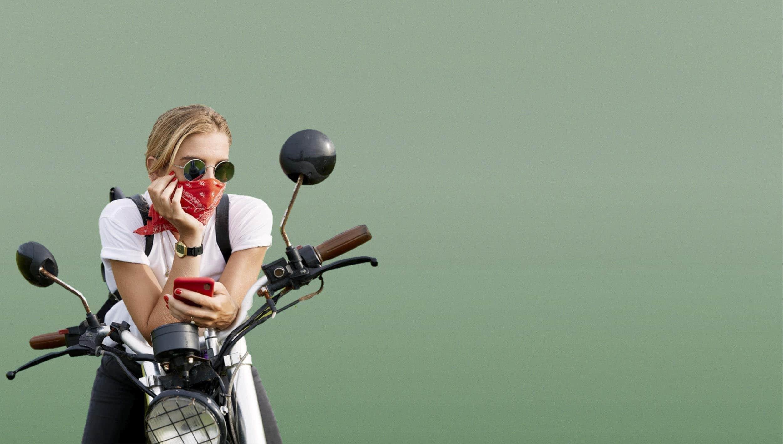 Mujer rubia con pañuelo rojo y gafas de sol, sentada en una moto custom sosteniendo un móvil rojo