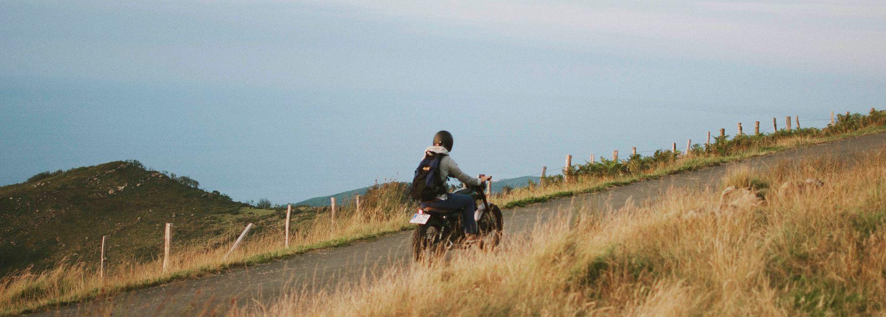 Plano aereo de una moto en carretera en medio de un bosque en otoño