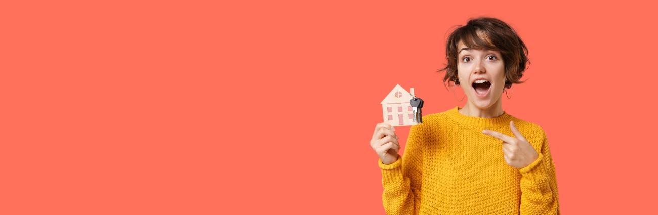 Mujer sonriente con jersey amarillo de punto sosteniendo las llaves de su nuevo piso