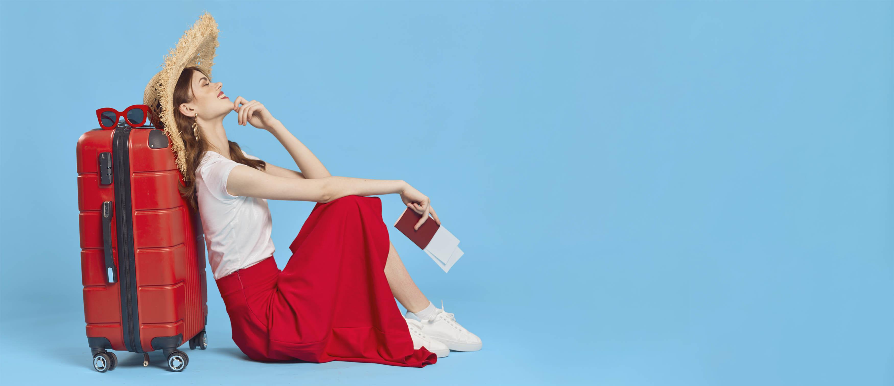Mujer con sombrero, camisa blanca y falda roja apoyada en una maleta roja