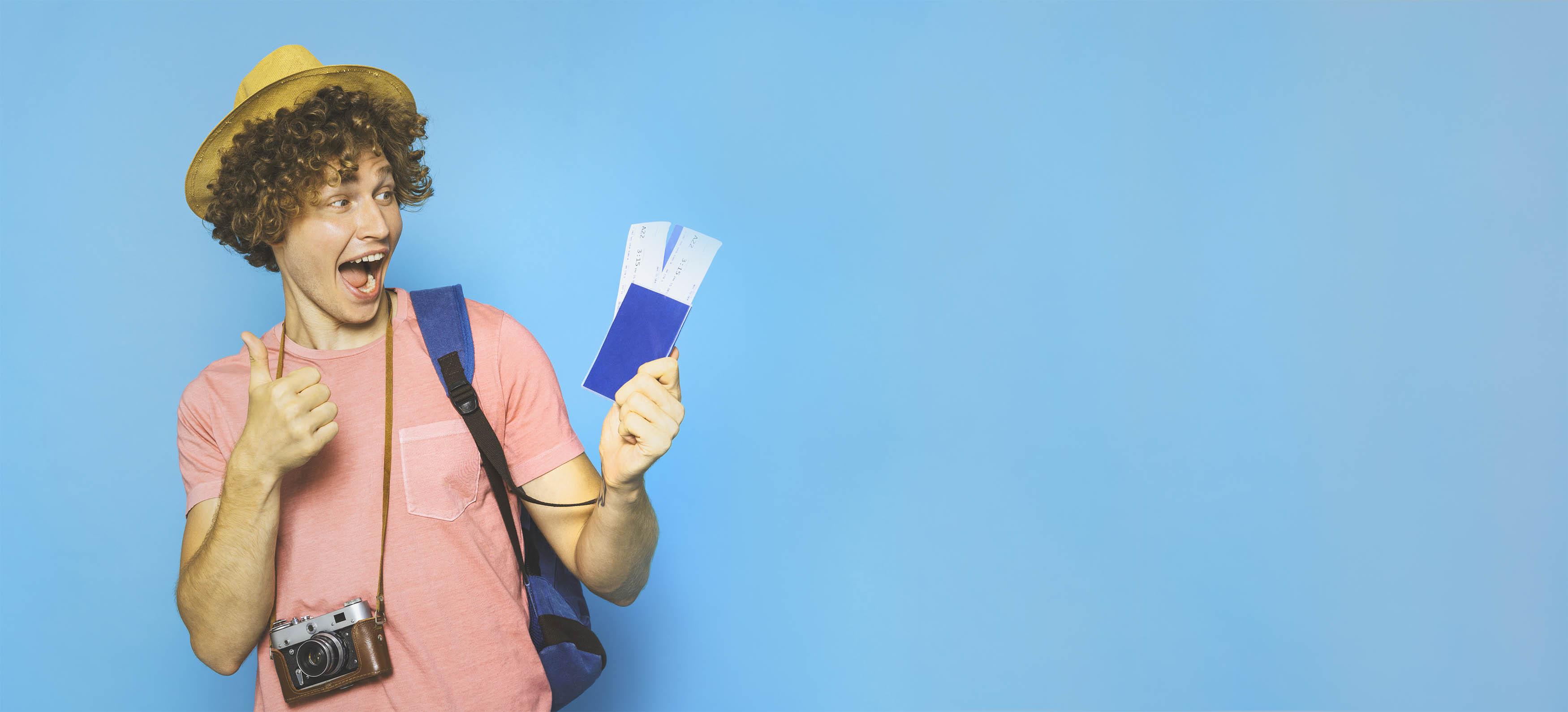 Chico rubio de pelo rizado con un sombrero y una cámara sosteniendo billetes de avión